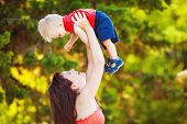 stock photo of woman red blouse  - A young mother-a woman with long chestnut colored hair,wearing a red blouse and her little boy-a boy with blond hair and grey eyes,wearing a red shirt with short sleeves, play and have fun together in the green of summer Park. ** Note: Soft Focus at 100% - JPG