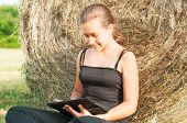 foto of haystack  - Young girl with device siting on the field close to haystack - JPG