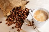 foto of hot coffee  - Cup of hot coffee on white wooden table and sack with coffee beans closeup - JPG