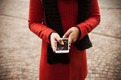 foto of porphyry  - Unrecognizable woman in the street using her mobile phone hands close up - JPG