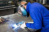 pic of welding  - professional welder welding metal pieces with light arc and sparks - JPG