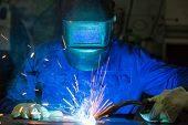 foto of welding  - professional welder welding metal pieces with light arc and sparks - JPG