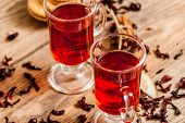 stock photo of hibiscus  - Glass cup of tea with hibiscus and lemon and cinnamon on wood table - JPG