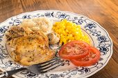 foto of southern fried chicken  - Chicken leg and thigh fried golden brown served in very country kitchen setting on old fashioned plate against rustic wood table top.  ** Note: Shallow depth of field - JPG