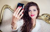 stock photo of bolivar  - Pretty model girl sitting on victorian sofa taking a selfie with phone - JPG