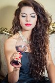 stock photo of bolivar  - Pretty model girl wearing blue dress sitting on victorian sofa holding a wine glass - JPG