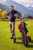 foto of golf bag  - a golf player playing on a beautiful golf course and a golf bag full of golf clubs - JPG