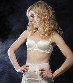 stock photo of stripping women window  - young sexy blond woman in  lingerie over dark background - JPG