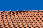 pic of red roof  - Red roof tile pattern over blue sky - JPG