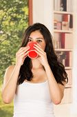 pic of early morning  - Female model in tank top early morning drinking coffee - JPG