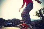 foto of skateboard  - skateboarder legs riding skateboard at skatepark ramp - JPG