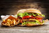 image of hamburger-steak  - Delicious hamburger and french fries on wooden background - JPG
