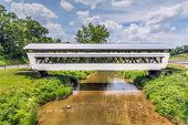 stock photo of awning  - The white Johnston Covered Bridge in rural Fairfield County Ohio has a window with an awning along its entire length on both sides - JPG