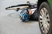 stock photo of accident victim  - Unconscious Male Cyclist Lying On Street After Road Accident - JPG