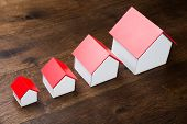 stock photo of row houses  - Different Size Houses In Row On Wooden Table - JPG