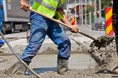 image of concrete pouring  - construction team pouring concrete on a road with boots and protection gear - JPG