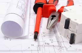 image of electrical engineering  - Rolled electrical diagrams electric fuse and work tools lying on construction drawing of house drawings for the projects engineer jobs - JPG