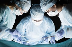 stock photo of operation theater  - Medical team performing operation - JPG