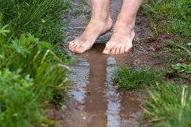 pic of barefoot  - feet of a young woman walking barefoot through the puddles - JPG