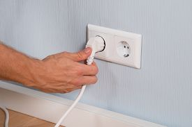 image of insert  - Closeup Of Hand Inserting An Electrical Plug Into A Wall Socket - JPG