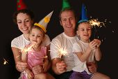image of new years baby  - family of four with sparklers on the birsday - JPG