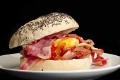 image of bap  - Bacon and egg roll with tomato sauce with a black background - JPG