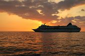 stock photo of cruise ship  - A beautiful Hawaiian sunset with a cruise ship setting out on its journey - JPG