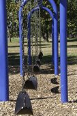 foto of swingset  - A swingset with mulch under neath in a public park - JPG