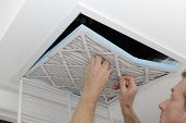 Person Removing An Old Dirty Air Filter From A Ceiling Intake Vent Of A Home Hvac System. Unclean Gr poster