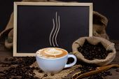 Coffee cup and coffee beans on wooden table. Coffee late art cup and Sack of coffee on old wood.