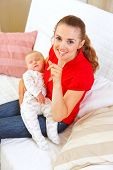 image of shhh  - Happy mother holding sleeping baby and showing shhh gesture - JPG