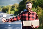 Man With Strict Face And Beard Travelling By Hitchhiking With Road On Background. Travelling And Hit poster