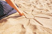 Unrecognizable Girl Draws A Sun With Sunbeams On Sand Beach With Her Finger, View Of Hand. poster