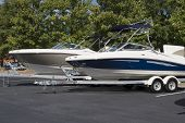 picture of ski boat  - Two luxury ski or fishing boats on trailers in a parking lot - JPG