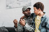 Father In Army Uniform And African American Boy Embracing And Talking At Home poster