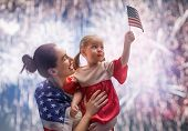 Patriotic holiday. Happy kid, cute little child girl and her mother with American flag. USA celebrat poster