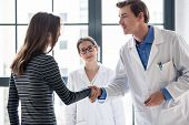 Young dedicated reliable physician and female patient shaking hands before consultation in the offic poster