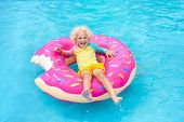 Child In Swimming Pool On Donut Float poster