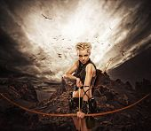 foto of archer  - Woman archer against storm over rocks - JPG