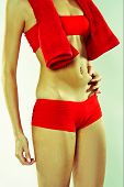 foto of partially clothed  - Woman In Red Active Wear Grabbing at Her Stomach - JPG