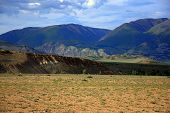 Pasture At The Foot Of A High Hill In A Valley Surrounded By Mountain Ranges. poster