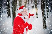 Santa Claus Blowing Magic Snow Of His Hands. Portrait Of Happy Santa Claus Walking In Snowy Forest A poster