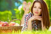stock photo of red hair  - Beautiful woman in the garden with apples - JPG