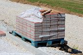 Wooden Pallet Partially Stacked With Grey And Red Rectangle Stone Tiles Covered With Nylon Protectio poster