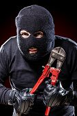 stock photo of wire cutter  - a burglar wearing a balaclava holding huge wire cutters over black background - JPG