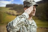 stock photo of beret  - Male army soldier in the uniform saluting - JPG