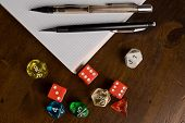 stock photo of tetrahedron  - Multicolored role play dice on wooden table top with role play accessories - JPG