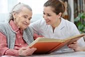 pic of hospice  - Senior woman and nurse looking together at album with old photographs - JPG