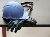 picture of hard_hat  - Blue hardhat and leather gloves at table - JPG