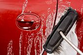 image of soapy  - Washing the car with a soapy brush at a coin operated car jet wash - JPG